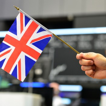 FRANKFURT AM MAIN, GERMANY - JUNE 24: A TV reporter pose with a Great Britain flag at the Frankfurt Stock exchange the day after a majority of the British population voted for leaving the European Union on June 24, 2016 in Frankfurt am Main, Germany. Many prominent corporate CEOs and leading economists have warned that a Brexit would have strongly negative consequences for the British economy and repercussions across Europe as well. (Photo by Thomas Lohnes/Getty Images)