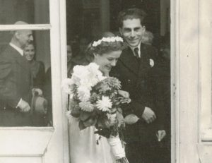 Laureen and Rudi Nussbaum leave Amsterdam City Hall after their wedding, Oct. 15, 1947. Otto Frank is behind the glass panel. (Courtesy of Laureen Nussbaum)